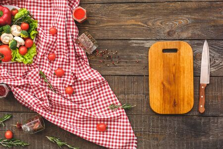 On a red towel chaotically lie vegetables, near lie knife, plate. Wooden background top view mock-up