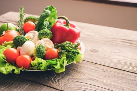 Vegetables lie on plate on the wooden table background top view. Healthy concept, colorful photo