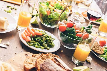 Different vegetables and healthy food with glasses of drinks on table at family banquet. Fresh and organic ingredients for meal at home Standard-Bild