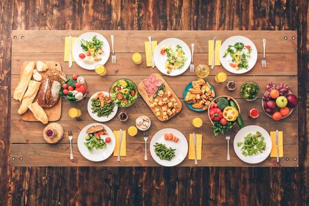 Large festive table with a huge amount of delicious and healthy food. Festive table set for six people. Wooden background top view mock-up. Wooden background top view mock-up