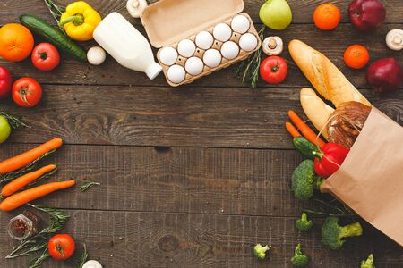 Flat lay view of raw organic vegetables with fresh ingredients for healthy cooking, eggs, bottle with milk and bread in paper bag on wooden table with copy space Standard-Bild