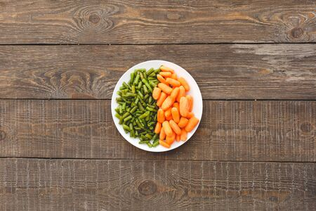 Flat lay view of plate with healthy and diet for, sweet carrot and green asparagus beans on wooden table with copy space