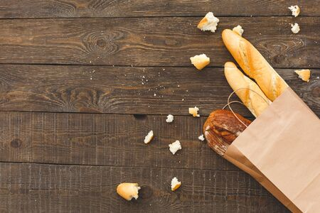Flat lay view of pack of crafting paper bag with different, tasty and fresh french baguette, bread on wooden table with copy space
