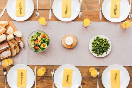 On the table is bread, salads , plate's and yellow napkins. Festive table set for six people. Wooden background top view mock-up