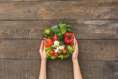 Flat lay view of woman holding plate with different raw and organic vegetables or fresh ingredients on wooden table with copy space