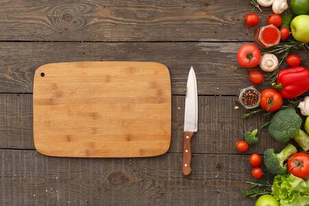 Flat lay view of chopping board and knife near ripe vegetables with fresh ingredients for healthy cooking on wooden table with copy space Stockfoto