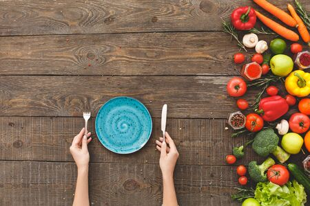 Woman holding fork, knife, in front of her blue plate and vegetables. Wooden background top view mock-up Stockfoto