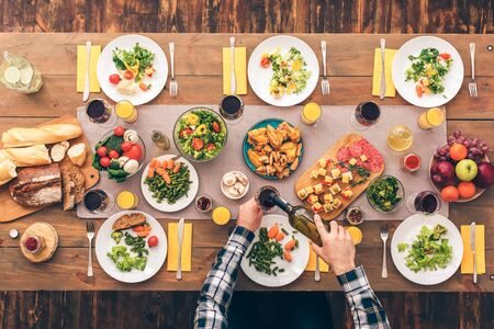 Man pours wine. Table with tasty and healthy dishes. Festive table set for six people. Wooden background top view mock-up Stockfoto