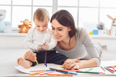 Motherhood. Mother lying with son sitting on floor drawing together with color markers smiling excited close-up