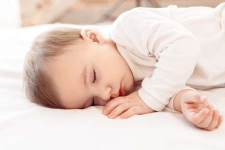 Little baby sleeping on bed at home close-up Stockfoto
