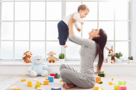 Motherhood. Mother sitting on floor lifting up son playing with bricks