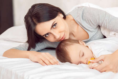 Motherhood. Mother smiling hugging baby with dummy sleeping lying on bed close-up Stockfoto