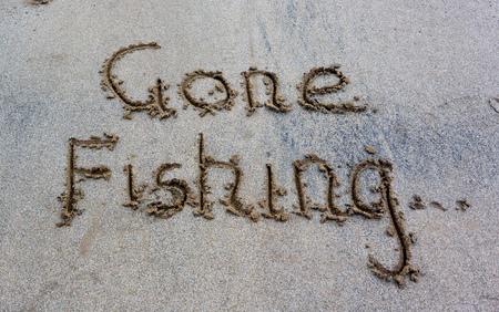 Gone fishing written in the sand