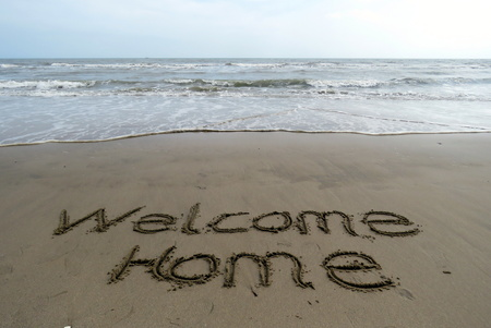 welcome home: Welcome home written in the sand on the beach Stock Photo