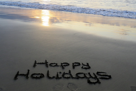 Happy Holidays Written in the Sand Stock Photo