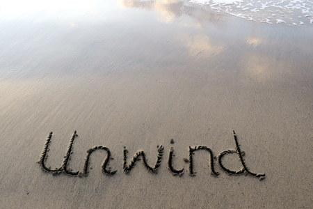 unwind: Unwind Written in the Sand Stock Photo