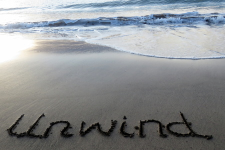 unwind: Unwind written in sand with waves approaching Stock Photo