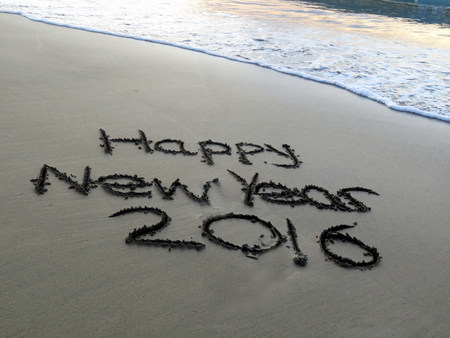 sand writing: Happy New Year 2016 Written in sand with waves approaching