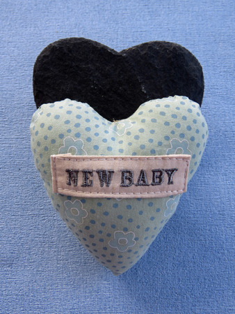A new baby small pillow with a black slate heart shape on a blue background