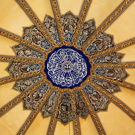 domes: Ornate decoration on the dome of a mosque, showing Islamic text.
