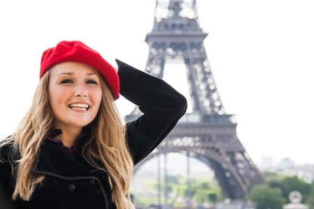 A Beautiful girl, wearing a red hat and smiling, in front of the Eiffel Tower  photo