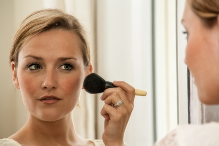 Womn applying blusher to her cheeks, reflected in a mirror photo