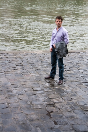 A man, with a sad expression, standing next to a canal  photo