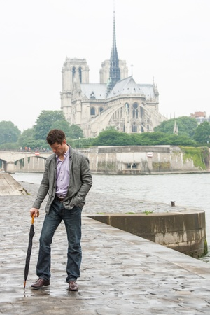 Sad man with an umbrella, standing in front of the Notre Dame Cathedral in Paris  photo