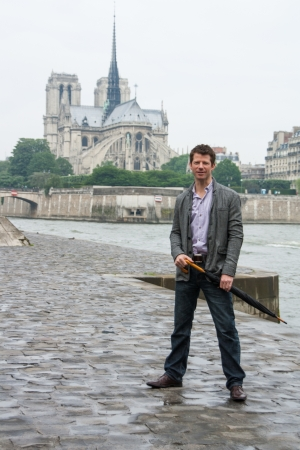 Man standing on a wet pathway beside the Seine in Paris  The Notre Dame Cathedral is in the background Stock Photo - 14928027