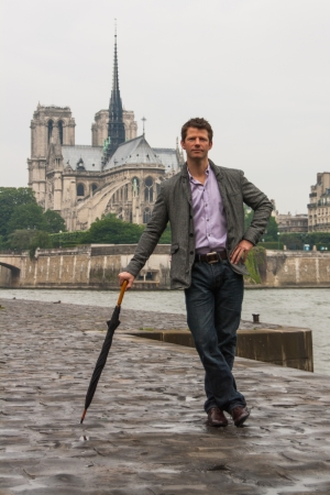Solemn-lookin man, leaning on an umbrella, waiting in front of the Notre Dame Cathedral in Paris  Stock Photo - 14927848