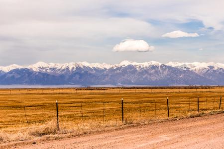 A view of the Rocky Mountains across farmland, in Colorado, USA