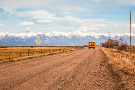 denver skyline with mountains: Mountain Valley, Colorado, USA, April 4, 2014. Yellow school bus on a country road with the Rocky Mountains in the background