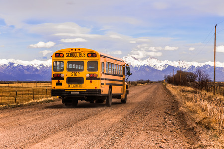 denver skyline with mountains: Yellow school bus on a country road, with snow-covered mountains in the background.