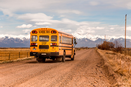 rural skyline: Yellow School Bus on a country road in Colorado.