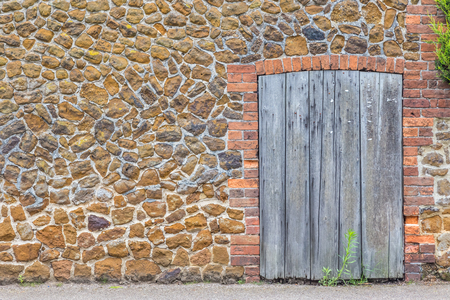 Ancient stone wall with a paneled wood door.