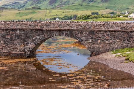 Eilean Donan Bridge reflected in the water of a loch in Scotland.