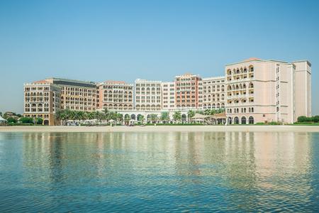 Abu Dhabi, United Arab Emirates, June 10, 2017: Ritz Carlton Hotel, Abu Dhabi, as seen from the water, with reflections. Editöryel