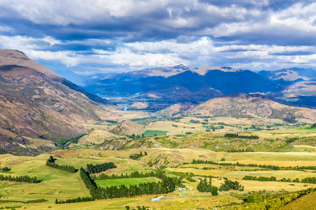 Aerial view from Crown Range Lookout in South Island, New Zealand, showing farmland surrounded by mountains.