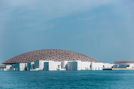 Abu Dhabi, UAE, April 27, 2018: View of the Louvre, Abu Dhabi, as seen from the from the sea, under a blue sky. Editöryel