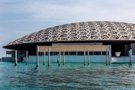 Abu Dhabi, UAE, April 27, 2018: View of the Louvre, Abu Dhabi, as seen from the from the sea,showing  the restaurant under the Rain of Light Dome.