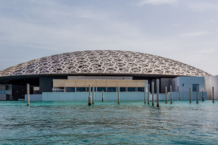 Abu Dhabi, UAE, April 27, 2018: View of the Louvre, Abu Dhabi, as seen from the from the sea,with the restaurant in the foreground.