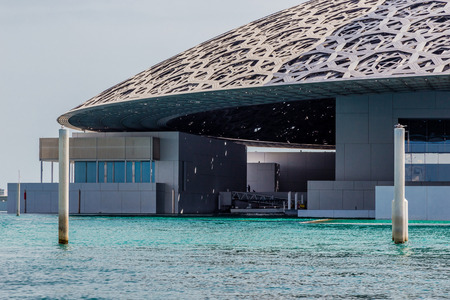 Abu Dhabi, UAE, April 27, 2018: Close up of the Louvre, Abu Dhabi, as seen from the from the sea, showing the reflections from the 'Rain of Light' Dome.