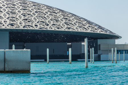 Abu Dhabi, UAE, April 27, 2018: Close up of the Louvre, Abu Dhabi, as seen from the from the sea, showing the Rain of Light Dome over the auditorium.