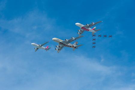 Emirates, Etihad, andAbu Dhabi, UAE, December 2, 2018: Air Arabia perform a flypast over the UAE with the Al Fursan aerobatic display team for National Day.