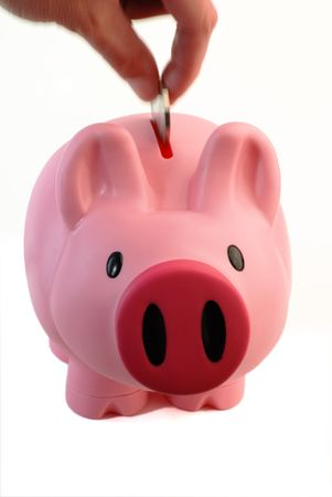 trotters: Dropping a coin into a pink piggy bank isolated on white