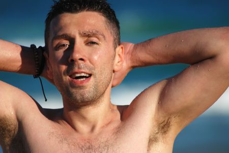 A gruff looking man stretches, wet from swimming. photo