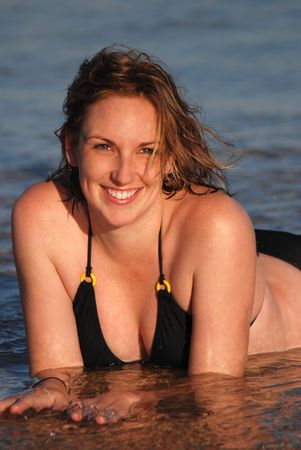 A beautiful young woman poses in shallows at the beach