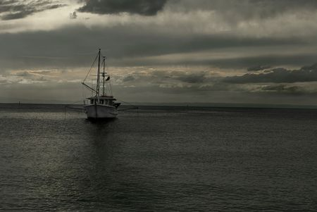 Fishing boat anchored in the bay at dusk photo