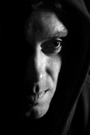 scared man: Hooded shadowed man  black and white image.