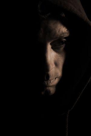 hooded: Depressed looking hooded man in shadow.